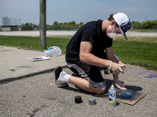 Sophomore Jonathan Gettler, 16, spray paints a stencil onto a sidewalk Thursday, May 26, 2016 near Riverview East High School in Marine City. Students in Jason Stier's art class are installing art projects and painting blighted structures along paths frequently used by students as part of a Safe Routes to Schools initiative.