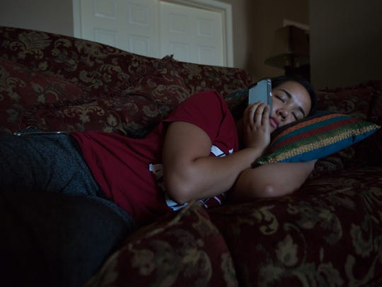 Brianna Gilligan, 17, of Las Cruces, curled up with