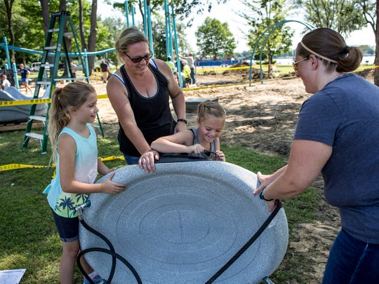 Emma Spresser, 7, Heather Stadler, Ella Paterson, 7, and Leah Spresser, all of Marysville, work on building a swing for a universally accessible playground Wednesday, July 20, 2016 at Marysville City Park. Ella raised $10,128 for the park through lemonade stands and bake sales and other fundraisers and donated the money to the city in 2014.