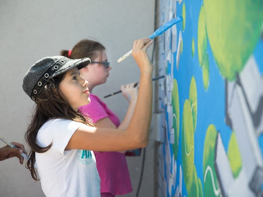 Luna Rodriguez, foreground, and Haley Spencer paint a tennis themed mural behind Laabs Pool on Saturday, Sept. 10, 2016, as part of an ongoing mural project of the City of Las Cruces Parks and Recreation Department's Youth Mural Arts Program.