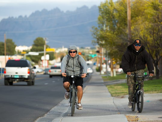 Alejandro Hernandez, left, and Osbaldo Valdez, both of Las Cruces, ride their bikes down East Idaho Avenue on Monday, Nov. 28, 2016,  with hoodies and hats on as temperatures become a bit cooler in the area.