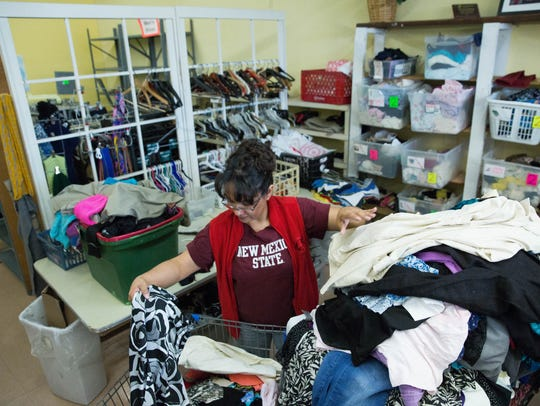 Alejandra Cisneros, a volunteer at the Gospel Rescue Mission Clothing Room, brings out sorted clothing that was newly-donated into the free clothing store where she will put it on hangers and get it out on the racks, Wednesday October 25, 2017.