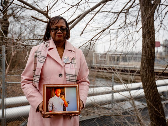 Shirley Mitchner holds a framed photo of her son Brandon at the exact location where he fell into the Grand River on June 29th, 2014.
