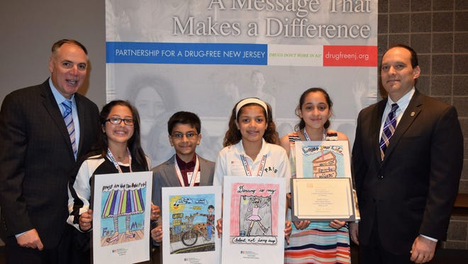Five Middlesex County students earned recognition as finalists in the Partnership for a Drug-Free New Jersey's Fourth Grade Folder Contest at an award ceremony Wednesday, May 3 at the Middlesex County Fire Academy in Sayreville. From left, Partnership for a Drug-Free New Jersey Executive Director Angelo Valente, Gwendolyn Negron of St. Joseph School in Carteret, Sanjay Ravishankar of Kennedy Park School #24 in Iselin, Lauren Daniels of Perth Amboy Catholic School, Jasiel Amigon of St. Joseph School in Carteret and Middlesex County Prosecutor Andrew C. Carey. Not pictured: Mylia C. Sanchez of Nathan Hale Elementary School in Carteret.
