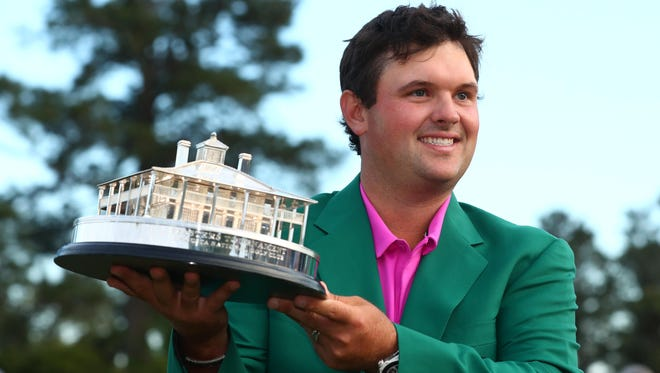 Patrick Reed holds up the trophy after winning the Masters by one stroke.