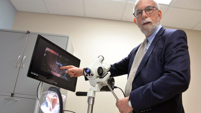 Dr. Martin Finkel talks about the colposcope, used for physical exams and imaging, during the open house for the new location of CARES Institute, Monday, Apr. 4 in Vineland.