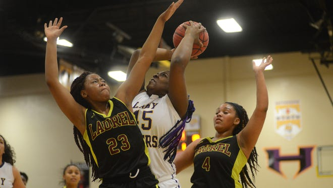 Hattiesburg's Dominique Poole takes a shot as Laurel defenders try to block Friday during their game Hattiesburg.