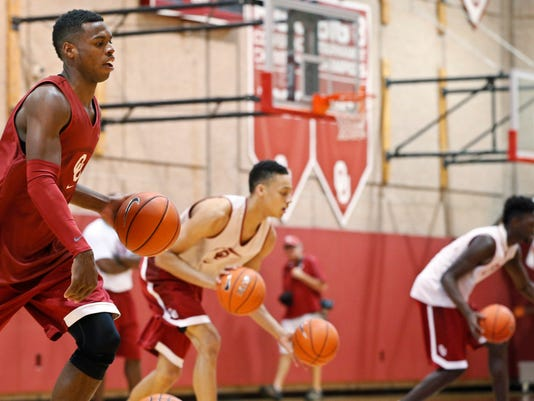 In this Monday, Oct. 27, 2014 photo, Oklahoma guard Buddy Hield, left, runs through a drill during an NCAA college basketball practice in Norman, Okla., Monday, Oct. 27, 2014. Oklahoma has high expectations with four starters back from last year's team that finished second in the Big 12. (AP Photo/Sue Ogrocki)