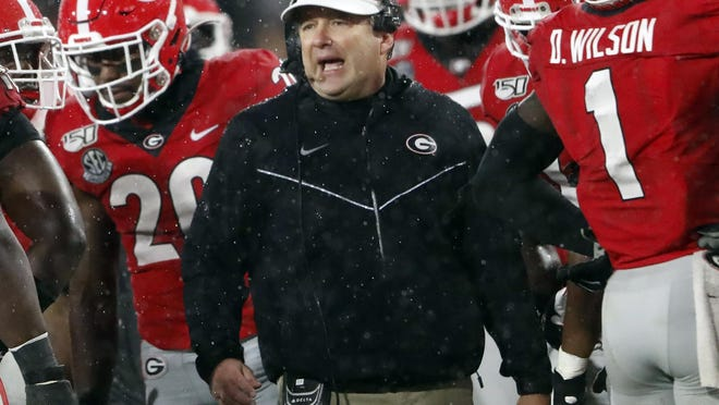 FILE - In this Oct. 19, 2019, file photo, Georgia coach Kirby Smart, center, talks to his players during a timeout in the first half of the team's NCAA college football game against Kentucky in Athens, Ga. There will be much interest in possible changes coming to No. 4 Georgia's offense with a new quarterback, who is expected to be Wake Forest transfer Jamie Newman, and a new coordinator, Todd Monken. Still, Smart's Bulldogs may lean on their experienced defense in the pandemic-delayed season.