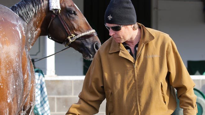 """Commanding Curve gets bathed on the backside of Churchill Downs by Dallas Stewart on Sunday. """"Nothing you can do, just bite your nails and wait, I guess,"""" Stewart said of the odds the horse will qualify for the Derby."""