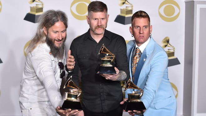 "Troy Sanders, from left, Bill Kelliher and Brann Dailor of Mastodon pose in the press room with the best metal performance award for ""Sultan's Curse"" at the 60th annual Grammy Awards at Madison Square Garden on Sunday, Jan. 28, 2018, in New York. (Photo by Charles Sykes/Invision/AP)"