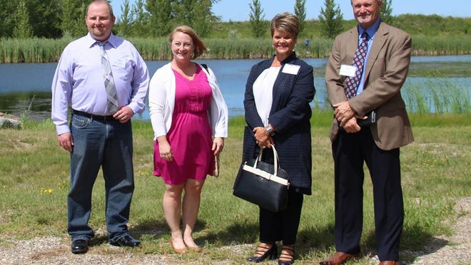 The four City of Crookston administrator finalists gather for a photo in front of one of the two ponds in Nature's View Estates. Left to right, they are Chase Waggoner, Amy Finch, Sally Dufner and Dana Schoening.