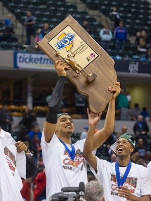 Arsenal Tech High School senior Trey Lyles (41) holds up the team's State Championship trophy after winning the IHSAA Boys Basketball 4A State Finals at Bankers Life Fieldhouse, Saturday, March 29, 2014. Aresnal Tech defeated Lake Central 63-59.