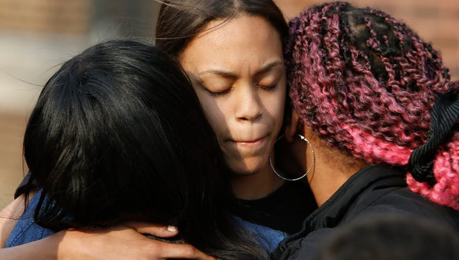 Mourners gather at Howard High School of Technology Thursday after a student died in a fight there.