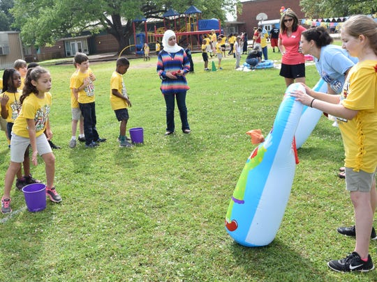 Cherokee Elementary School second-grader Arianna Bates (left) tosses a bean bag into the mouth of a blow-up clown held by fifth-grader Savannah Woodruff, who is helping with the school's field day Thursday.