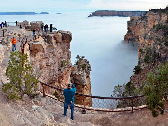 Visitors to Mather Point on the South Rim of the Grand Canyon view a rare weather phenomenon: a sea of thick clouds filling the Canyon just below the rim on Thursday, Dec. 11, 2014. Cory Mottice of the National Weather Service said the weather event happens about once every several years, though the landmark was treated to one last year.