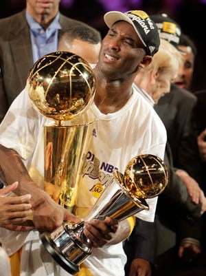 Los Angeles Lakers guard Kobe Bryant holds the Larry O'Brien trophy, left, and the most valuable player trophy after winning the NBA Finals in June, 2010,.