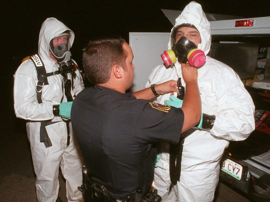 In this 1998 photo, Drug Enforcement Administration agents put on protective suits before checking for fumes and damage at a suspected meth lab in Springfield.