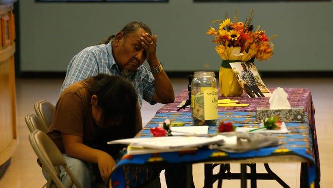 Charley P. Joe and his grandson, Alex Joe, mourn the loss of Jonathan Joe during a meeting Monday at the Shiprock Chapter house.