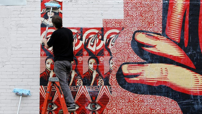 Artist Shepard Fairey works on a mural in Silverton, one of many that will be situated throughout the Tri-State sponsored by CAC.