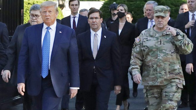 """FILE - In this June 1, 2020 file photo, President Donald Trump departs the White House to visit outside St. John's Church, in Washington. Part of the church was set on fire during protests on Sunday night. Walking behind Trump from left are, Attorney General William Barr, Secretary of Defense Mark Esper and Gen. Mark Milley, chairman of the Joint Chiefs of Staff.  Milley says his presence """"created a perception of the military involved in domestic politics."""" He called it """"a mistake"""" that he has learned from."""