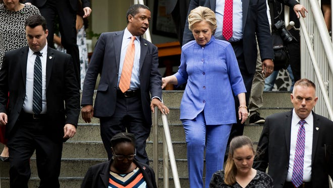 Democratic presidential candidate Hillary Clinton, right, speaks with Traveling Political Advisor Darren Peters, center left, as she leaves an early voting brunch at Fado Irish Pub in Miami, Sunday, Oct. 30, 2016. (AP Photo/Andrew Harnik)