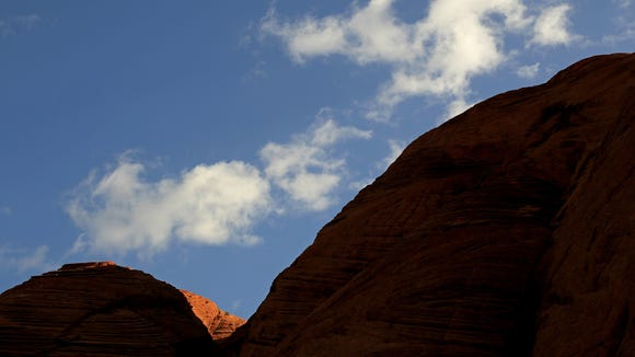 The low morning sun casts the cliffs of Snow Canyon State Park along the Butterfly Trail into near-silhouette.