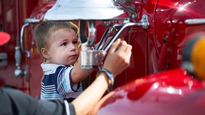 Uriah Taylor, 3, of Henrietta rings a bell on a fire truck at a Kids and Trucks event at Frontier Field on Saturday, September 26, 2015.