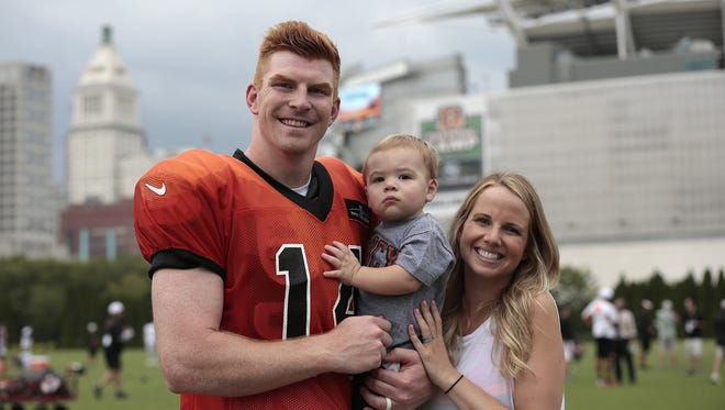 Cincinnati Bengals quarterback Andy Dalton and his wife Jordan pose with their son Noah after practice at the Bengals training facility next to Paul Brown Stadium Monday, Aug. 17.