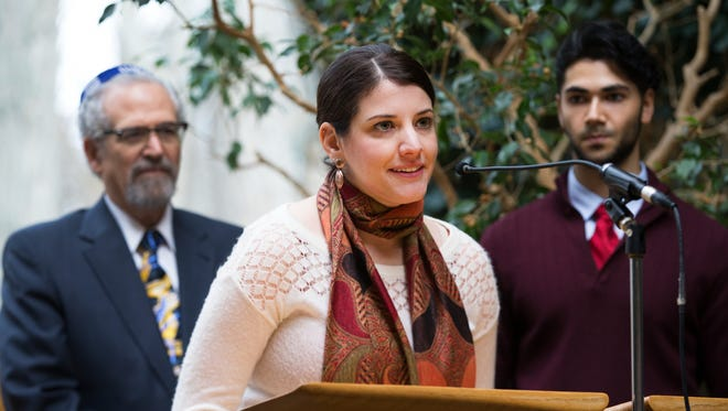 Megan Robinson with the Catholic Diocese of Rochester leads a reading from the Book of Numbers in English from the 141st Union Thanksgiving Service at Temple Sinai in Rochester on Thursday, November 26, 2015. Rabbi Alan Katz also lead the reading in Hebrew and Husain Bawany read it in Arabic.