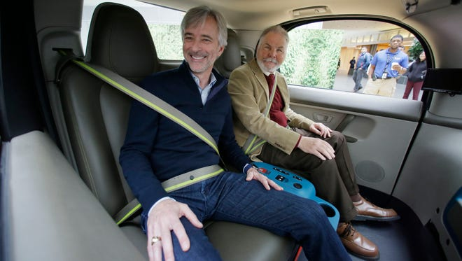 Waymo CEO John Krafcik, left, sits with Steve Mahan, who is blind, inside a driverless car during a Google event, Tuesday, Dec. 13, 2016, in San Francisco. The self-driving car project that Google started seven years ago has grown into a company called Waymo.