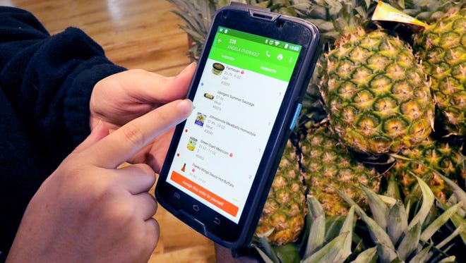 Courtney Jeanpierre uses a smartphone app that lists a customer's online grocery order that is organized to route her through the store in a continuous loop at Albrecht's Delafield Market.
