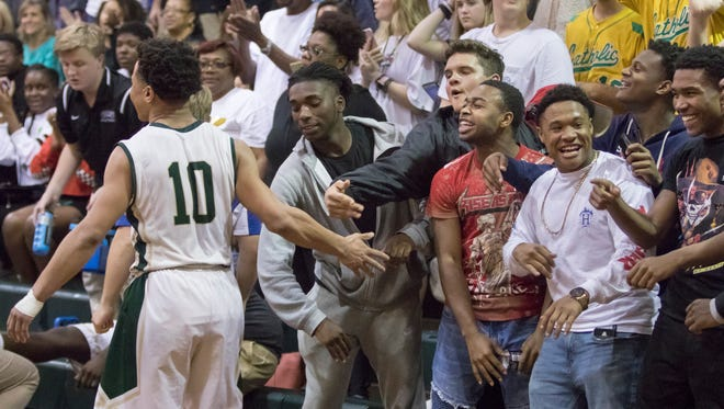 Damarious Nickerson (10) high fives the crowd as he goes to the bench at the end of the 66-41 Catholic victory over Bolles in the Region 1-5A final basketball game at Catholic High School on Friday, March 2, 2018.