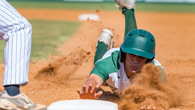 Rams shortstop Cole Romero dives back to first ahead of the pick off throw as Acadiana takes on HL Bourgeois Baseball. Tuesday, April 24, 2018.