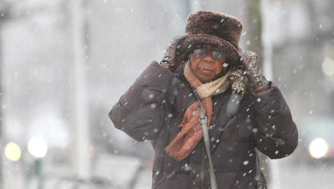 Inez Wright of Tarrytown protects her face as the wind kicks up from a winter storm.