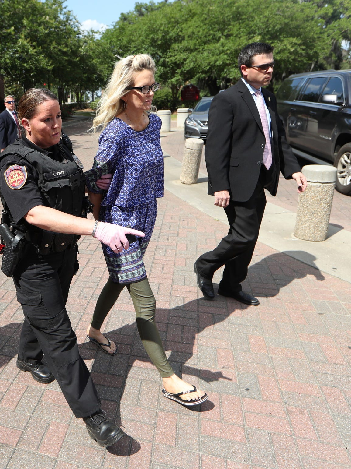 Denise Merrell Williams, 48, is led out of her accounting office at Doak Campbell Stadium in handcuffs on May 8, after a Leon County grand jury indicted her on a charge of first-degree murder of Mike Williams.