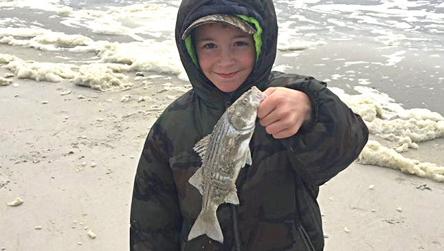 Michael with a small striper he caught on Easter Sunday.