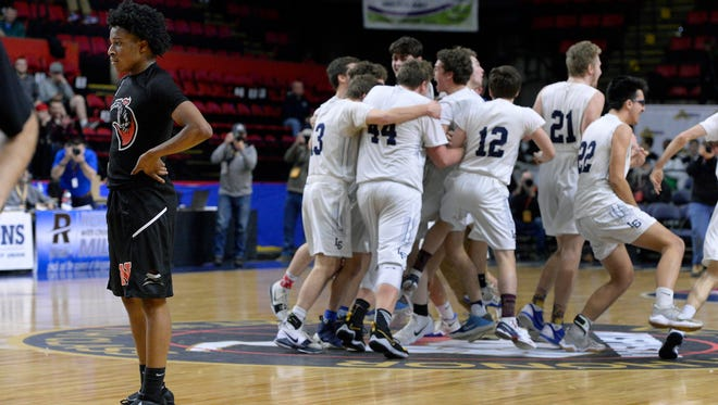 Northstar's Michael Brown reacts at the final buzzer as Lake George players celebrate their state title during the Class C final at the 2018 NYSPHSAA Boys Basketball Championships, Saturday, March 17, 2018, in Binghamton, N.Y. Northstar Christian Academy's season came to an end with a 66-65 loss to Lake George-II.