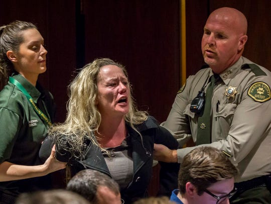 A woman is escorted out of court for an outburst during