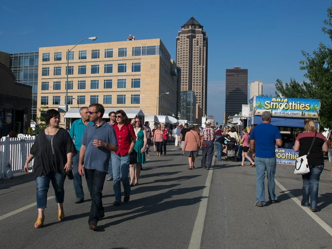 A crowd walks down the street during the Des Moines