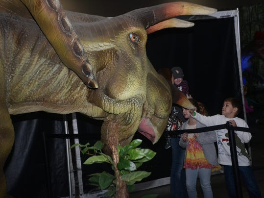 """ANI Discover the Dinosaurs Patton Ferguson (right) and his cousin Isabella McLain (left0 touch a replica of a triceratops at Blue Star Media's """"Discover the Dinosaurs"""" exhibit held Saturday, Nov. 23, 2014 at the Alexandria Riverfront Center in downtown A"""