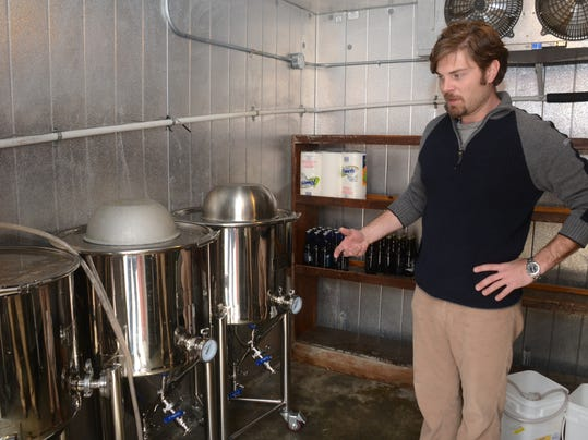 ANI Broken Wheel Brewery John Knoll (left), owner of Broken Wheel Brewery in Marksville, shows where the beer brewed is fermented. The brewery operates out of the Fresh Catch Bistreaux which is also owned by Knoll. Thursday, Feb. 19, 2015.-Melinda Martinez