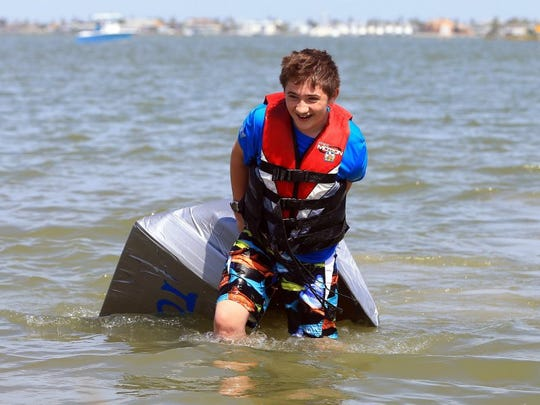 GABE HERNANDEZ/CALLER-TIMES Simon Proctor drags his cardboard boat to shore after it sank while he competed in the cardboard boat race during the 42nd Annual Rockport-Fulton Seafair on Saturday, Oct. 8, 2016, in Rockport.