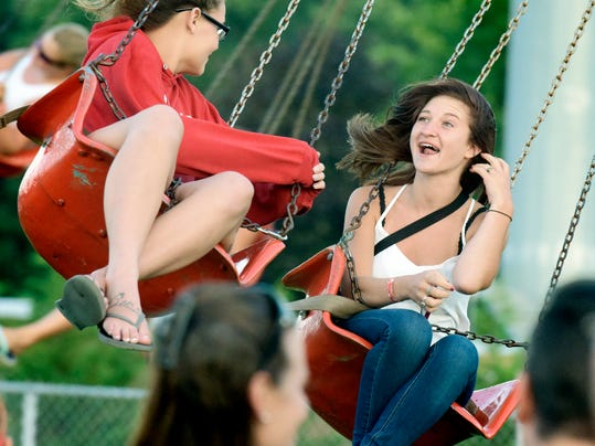 Kayla Dohn, 17, and Aspyn Pangle, 18, left, both of York City, ride the Swinger during Eureka Volunteer Fire and Ambulance Company's annual summer carnival Wednesday, July 15, 2015. The event runs through July 23 at the Stewartstown Community Grounds. Bill Kalina - bkalina@yorkdispatch.com