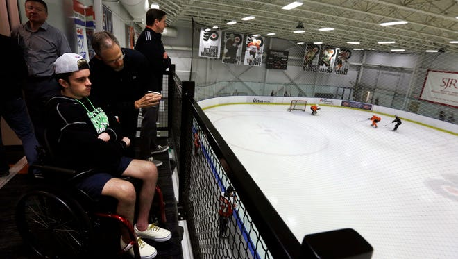Flyers assistant general manager Chris Pryor, center, talks with Ryan Straschnitzki at the Skate Zone Friday.