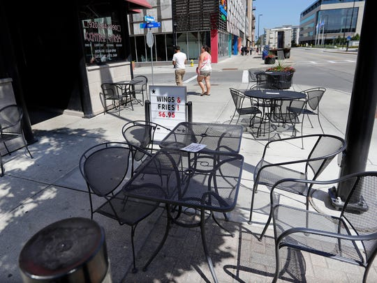 Pedestrians walk past tables and chairs on the sidewalk