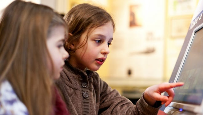 Two young girls are using a touch screen visual aid in a museum, Lyme Regis, Dorset, UK