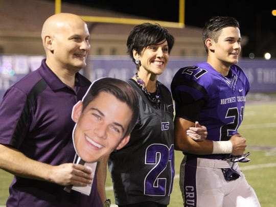 Northwest Christian senior Bronson Sanich walks out with his parents before a football game in Phoenix, Arizona on Oct. 30, 2015.