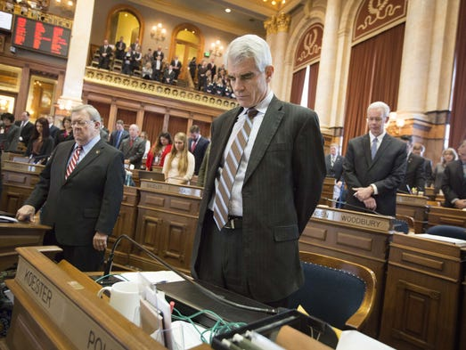 Rep. Kevin Koester bows his head in prayer during the