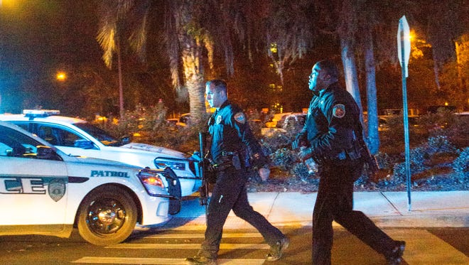 Police officers carrying assault rifles walk near Strozier library on the main campus of Florida State University on Thursday, Nov. 20, 2014 in Tallahassee, Fla.